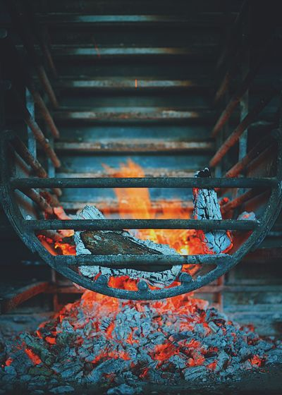 Close-up of burning firewood on metal grate at fireplace