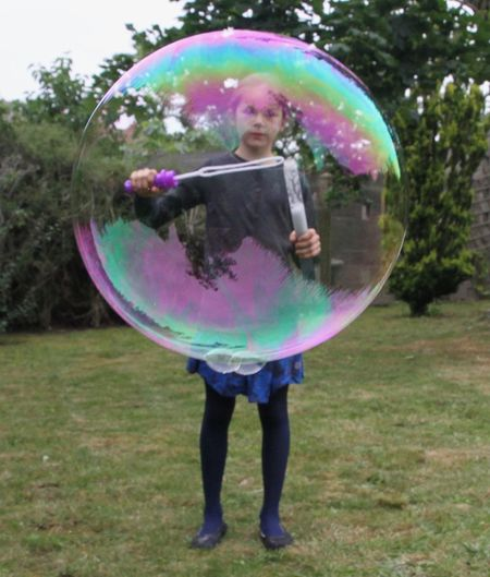 Full length of boy playing with bubbles