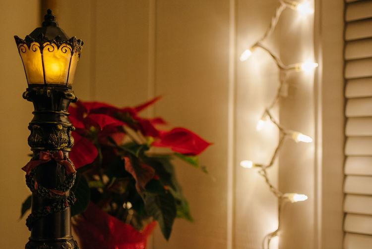 Close-up of illuminated lamp hanging against wall at home