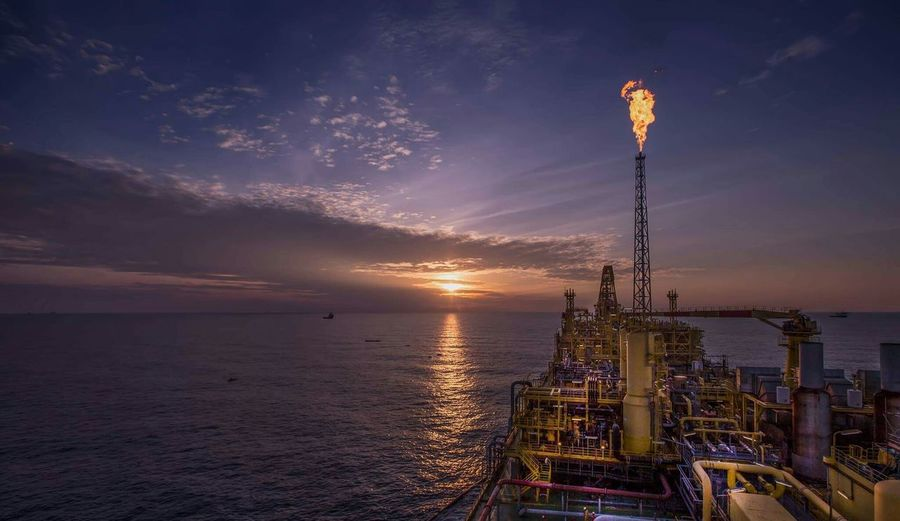 Oil rig over sea against sunset sky