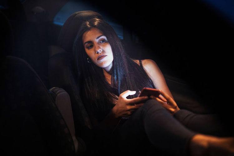 Young woman using smart phone sitting in darkroom
