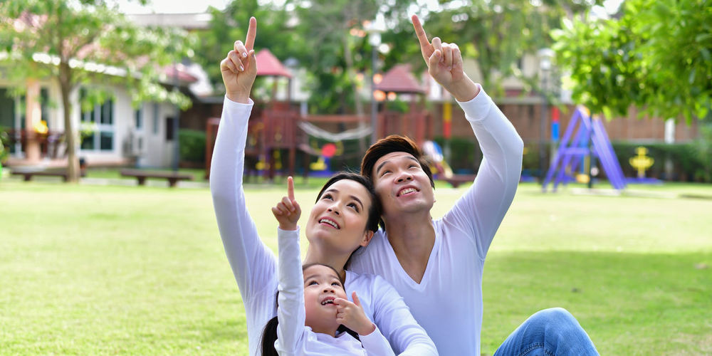 Family pointing while sitting at park