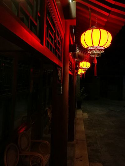 Courtyard and lanterns Illuminated Hanging Lighting Equipment Lantern In A Row Outdoors Red Chinese Lantern Courtyards Building Exterior Diminishing Perspective