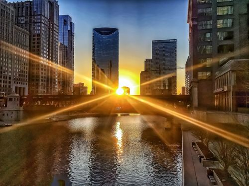 Sunbeams are covering a view of a Chicago River sunset in February. El Train Track Elevated Bridge Rush Hour Winter Riverwalk Sunset River Downtown Loop Chicago Architecture Sunset Building Exterior Built Structure City Lens Flare Sun Skyscraper Sunbeam Sky Reflection Sunlight Outdoors City Life Water Cityscape Nature