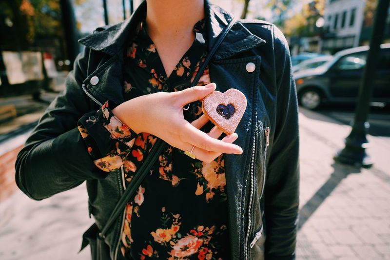 Midsection Of Woman Holding Heart Shape Cookie While Standing On Street