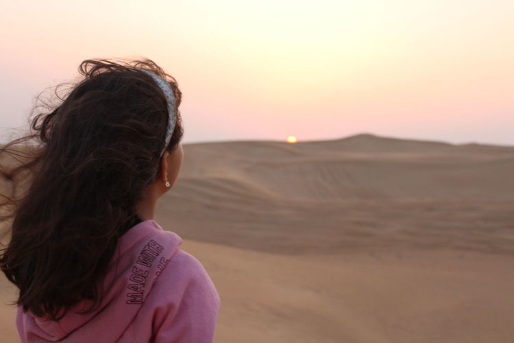 Girl looking at sunset at dubai's desert