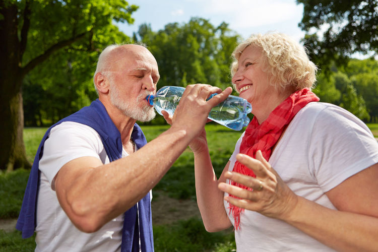 Senior Couple Drinking Water At Park