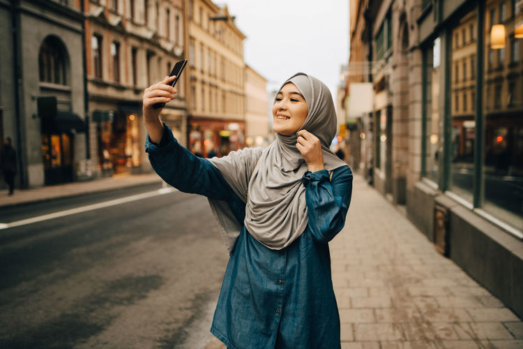 Young woman photographing while standing on street in city