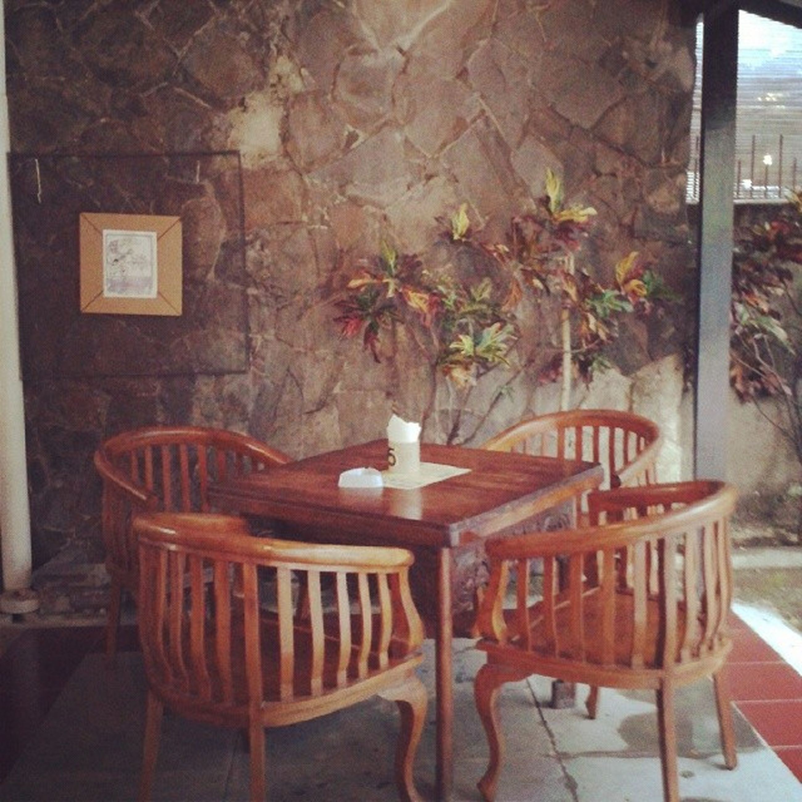 chair, indoors, absence, table, empty, furniture, seat, home interior, wall - building feature, architecture, built structure, illuminated, potted plant, wall, window, house, no people, lighting equipment, restaurant, wood - material