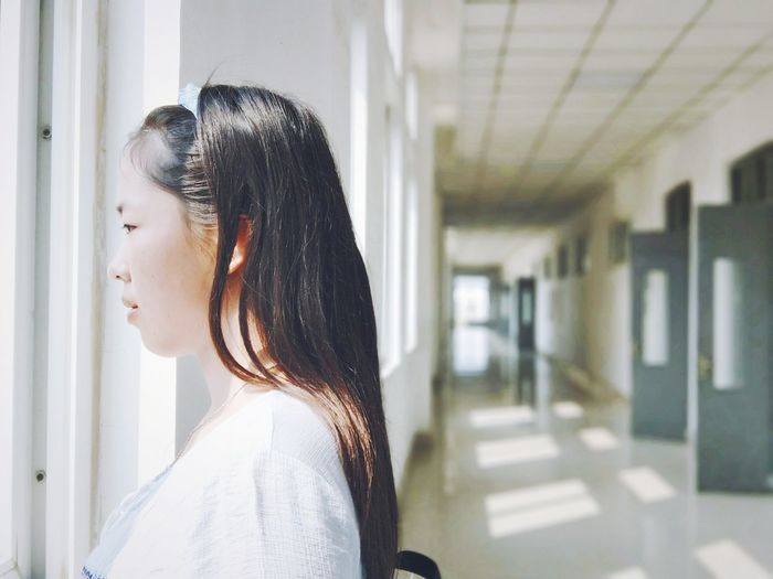 Profile View Of Young Woman Looking Through Window In Corridor