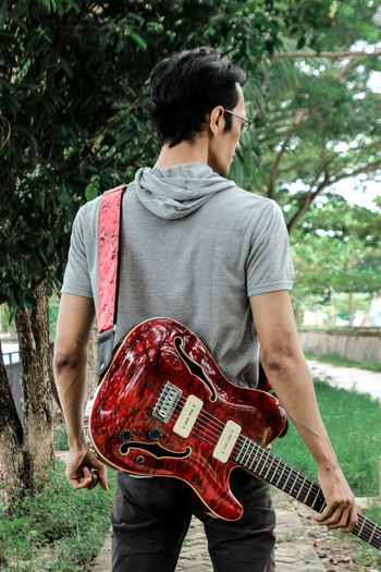 Rear view of man holding guitar