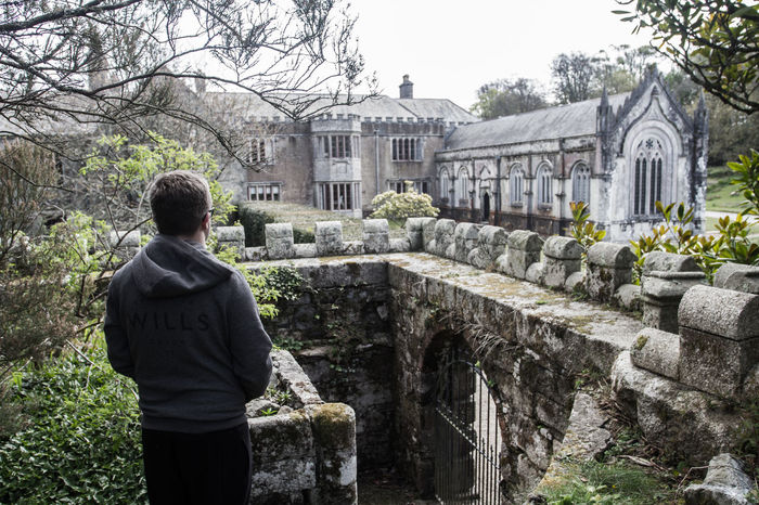 A young man standing and looking at an ancient mansion house in a scene reminiscent of a video game such as Tomb Raider.Architecture Building Exterior Built Structure Cemetery Day History Lifestyles Men One Person Outdoors People Real People Rear View Sky Spirituality Standing Tree Young Adult Mansion Mansion House Tombraider Tomb Raider  Atmospheric Dark Adventure