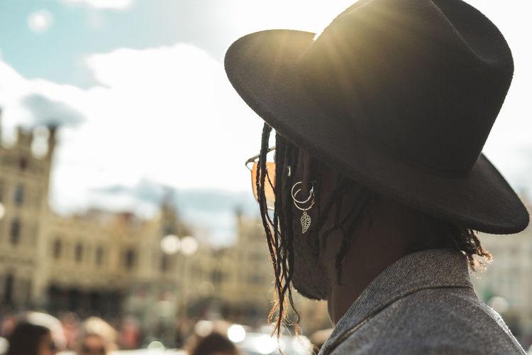 Portrait of woman wearing hat against sky in city