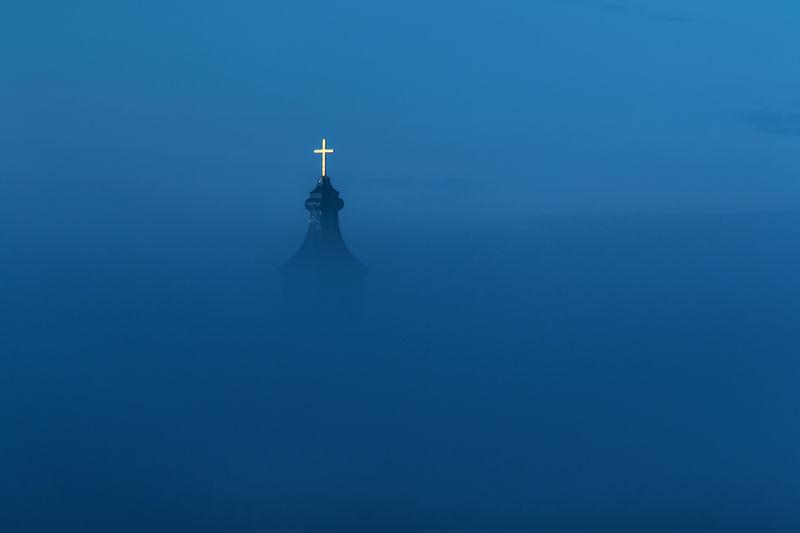 Cross on tower amidst fog