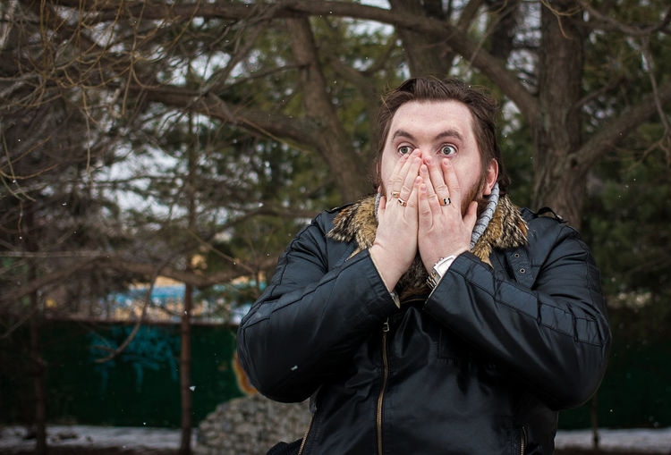 Shocked man with hands covering mouth against trees during winter at park