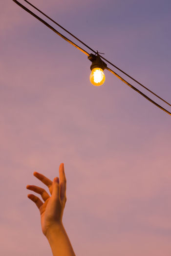 Low angle view of hand holding light bulb against sky during sunset