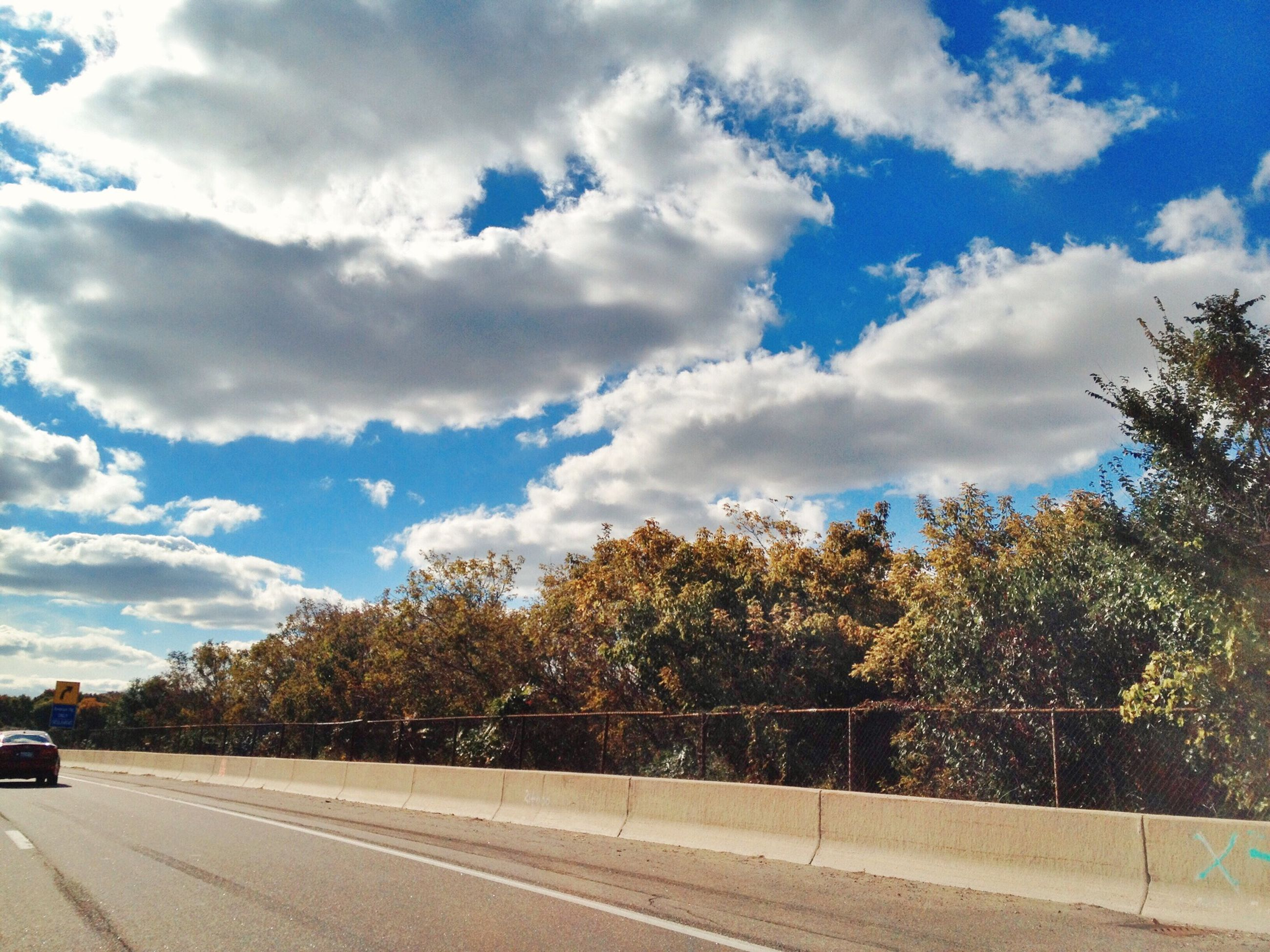 transportation, tree, road, sky, cloud - sky, road marking, the way forward, land vehicle, car, street, mode of transport, cloud, nature, growth, sunlight, day, country road, cloudy, outdoors, blue