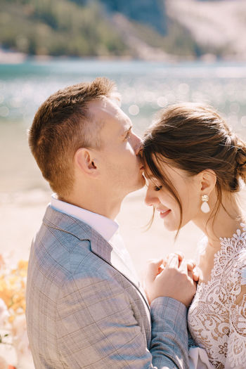Smiling bridegroom embracing while standing outdoors