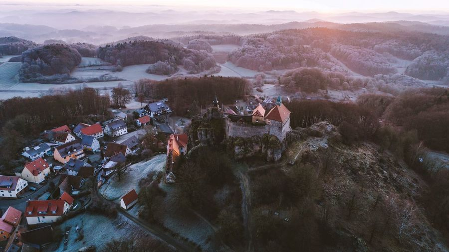 Sunrise over the castle on the hill. High Angle View Architecture Building Exterior House Built Structure Outdoors Nature Mountain Sunset Beauty In Nature Town Scenics Mountain Range Roof Cold Temperature Winter No People Day Tree Domestic Animals