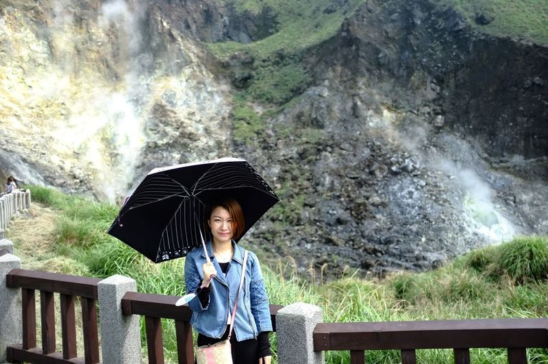 Portrait of young woman with umbrella standing against mountains