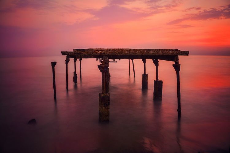 Broken Pier In Sea At Sunset
