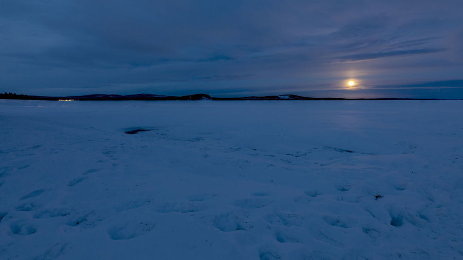 Scenic view of frozen lake against sky at dusk