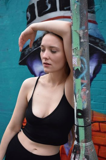 Tired young woman leaning on pole against wall