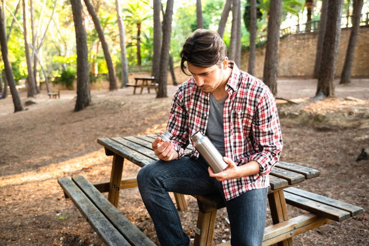 Young man sitting on bench at park