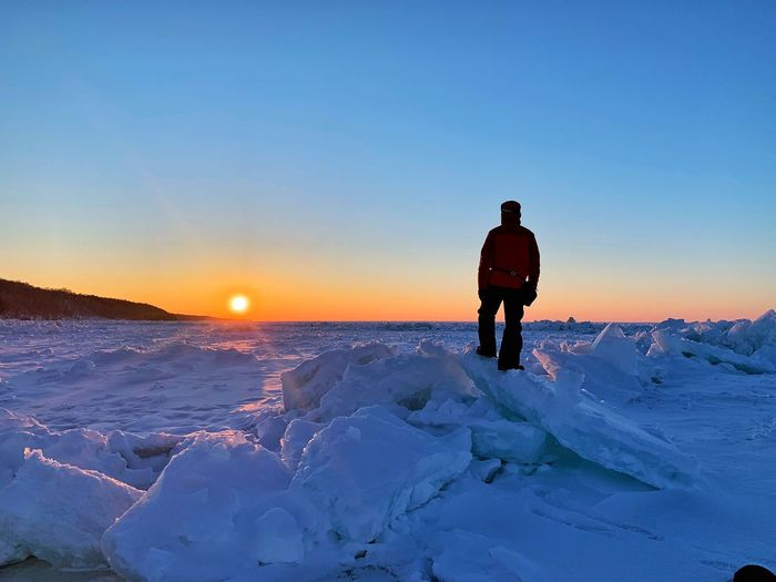 Rear view of man standing on snow against sky during sunset