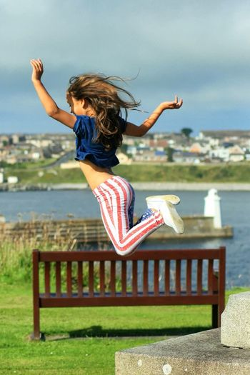 Full Length Of Woman Jumping By Park Bench On Sunny Day