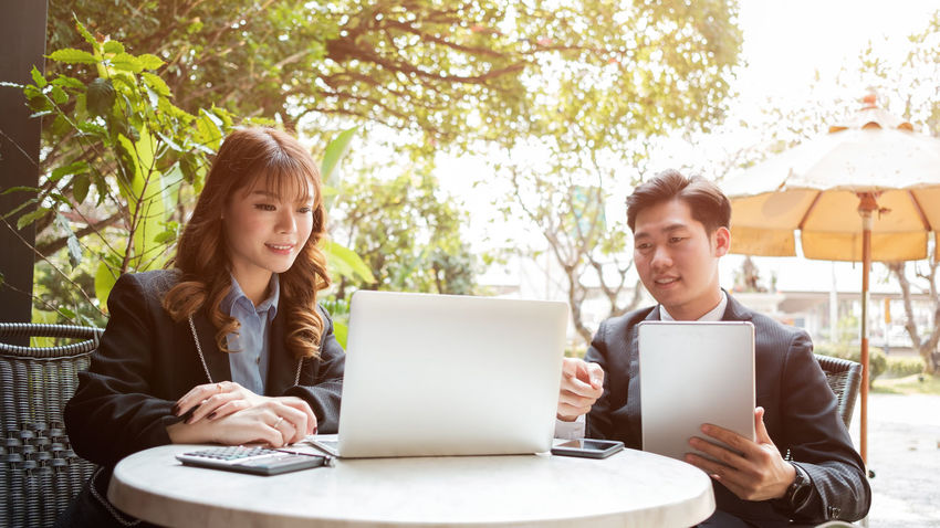 Business Businessman Businesswoman Colleague Communication Computer Connection Convenience Coworker Day Internet Laptop Portability Sitting Smiling Teamwork Technology Togetherness Two People Using Laptop Wireless Technology Working Young Adult Young Men Young Women