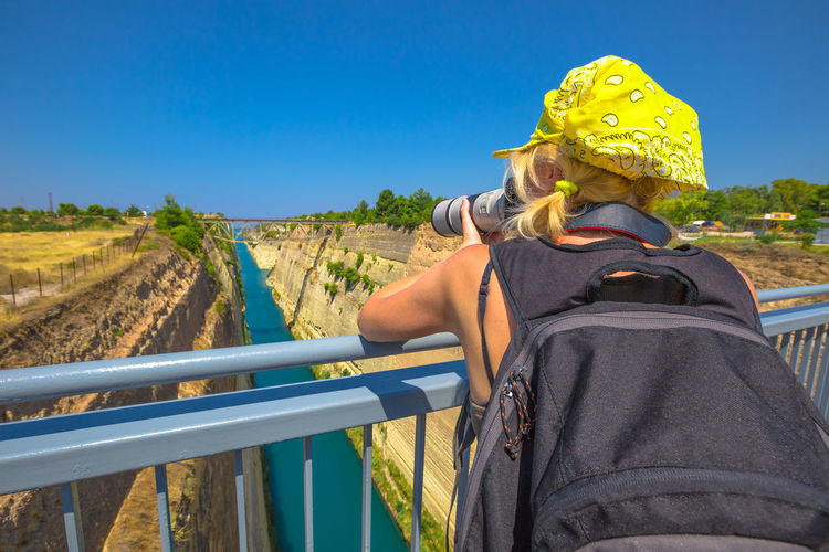 Rear view of woman photographing while standing on bridge against clear blue sky
