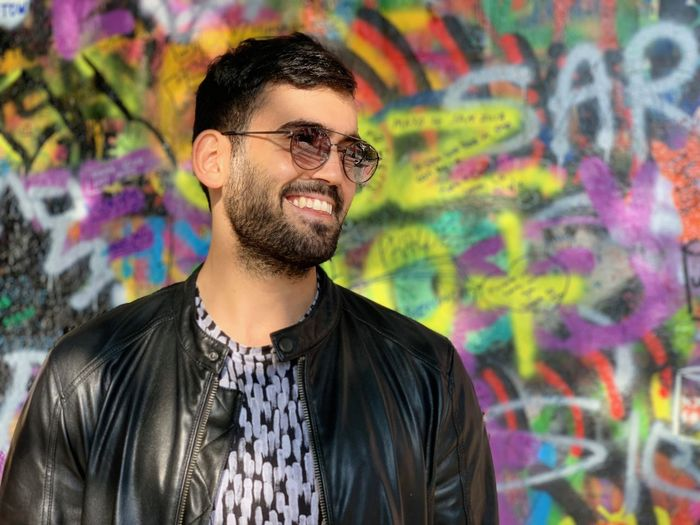 Glasses Young Men One Person Young Adult Beard Portrait Front View Smiling Facial Hair Graffiti Casual Clothing Eyeglasses  Happiness Waist Up Real People Standing Headshot Multi Colored Fashion Outdoors Human Face Moments Of Happiness