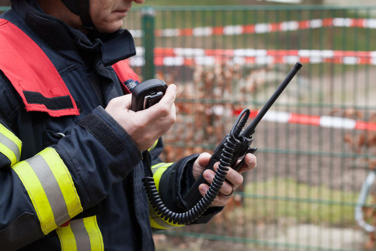 Firefighter standing with walkie-talkie outdoors