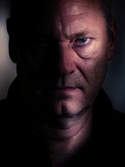 Close-up portrait of serious man in darkroom