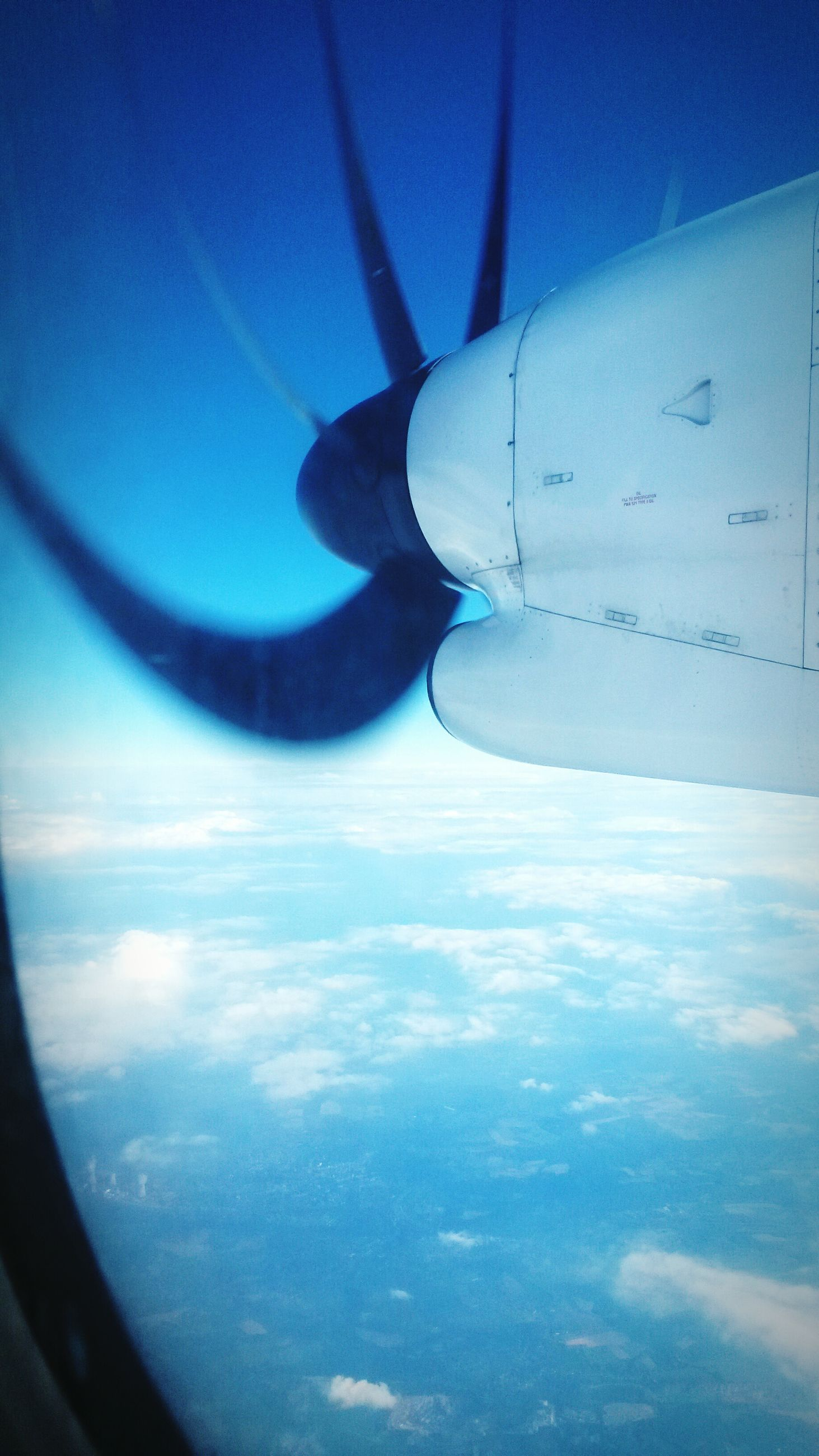transportation, airplane, mode of transport, air vehicle, flying, blue, aircraft wing, part of, cropped, travel, mid-air, aerial view, vehicle interior, sky, journey, transparent, on the move, vehicle part, window, glass - material