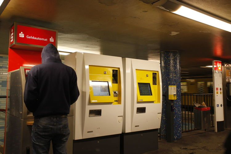 Kunde am Geldautomaten im Bahnhof Cashpoint Machine Day Indoors  Men One Person Pay Phone People Public Transportation Real People Rear View Standing Subway Station Technology Three Quarter Length Ticket Machines U Bahnhof Vending Machine Yellow