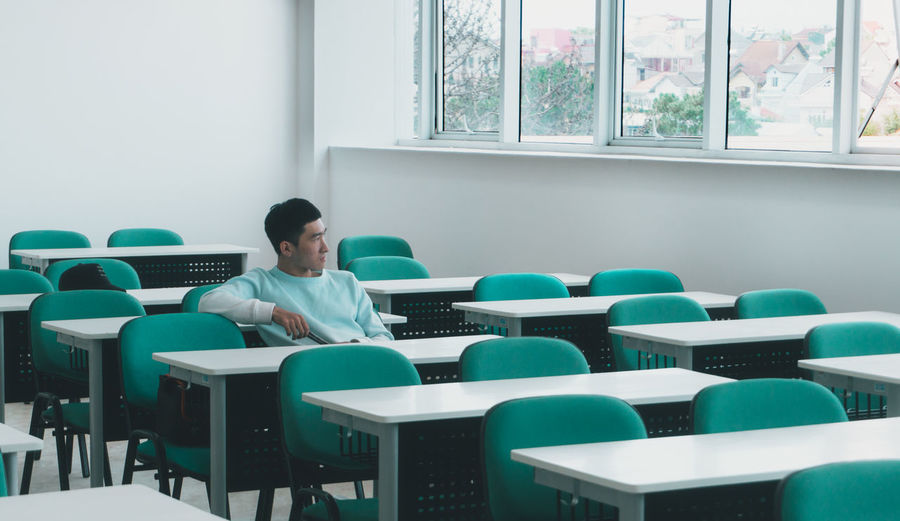 Young man looking away while sitting on table in classroom