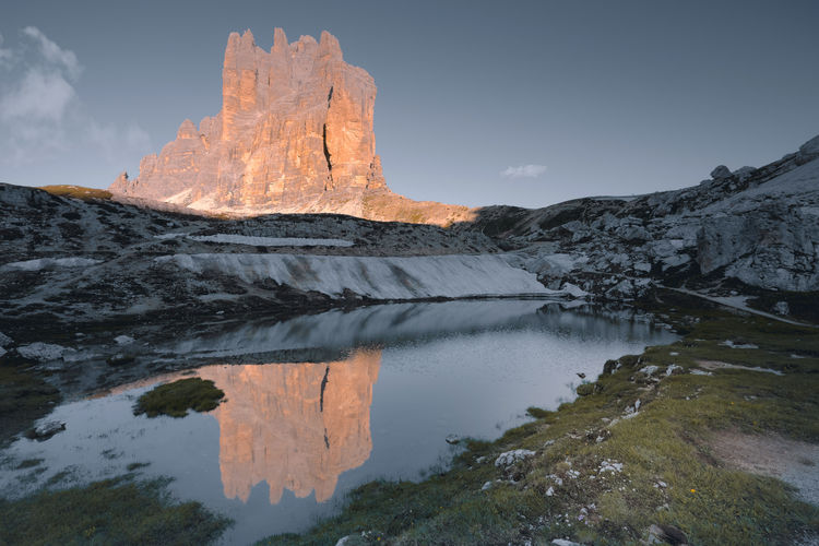 The drei zinnen / tre cime di lavaredo enlightened by the morning sun reflecting in a mountain lake.