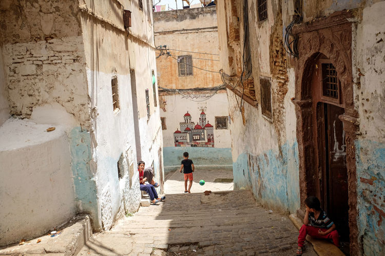 People on alley amidst buildings in city
