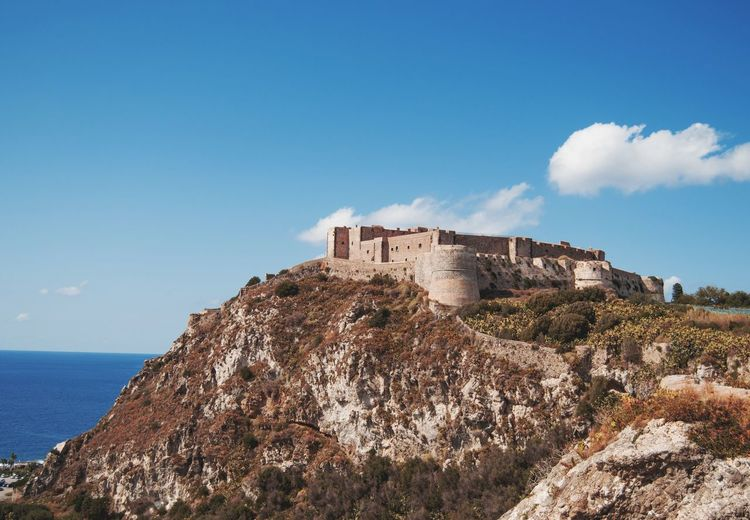 Castle by sea against blue sky in sicily