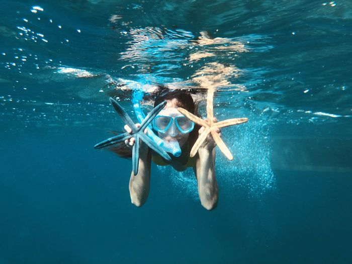 Portrait of woman holding starfish while snorkeling in sea