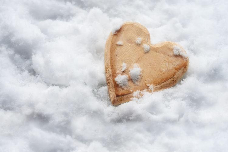 Heart shape on snow against sky