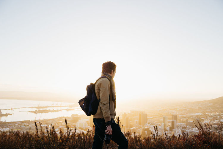Tim and the city. Adult Adventure Backgrounds Backpack Beauty In Nature City Cityscape Clear Sky Day Jonnynichayes Leisure Activity Lifestyles Mountain Nature One Person Outdoors People Photographing Real People Rear View Scenics Sky Standing Sunset