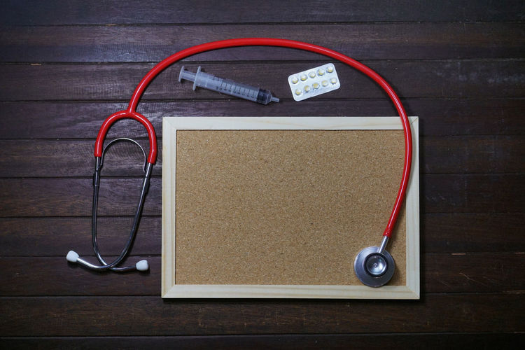High angle view of picture frame with syringe and stethoscope on wooden table