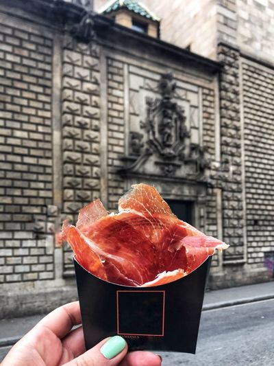 Black paper bag with jamon in hand against the background of a beautiful old stone wall. Street food, thinly sliced jamon in a paper bag makes it possible to have a tasty and satisfying snack during a walk and sightseeing of Barcelona. Delicious Foodie Eating Barcelona Spanish Food Spanish Traditional Food Traveling Meat! Meat! Meat! Ham Jamon Street Food Human Hand Hand Holding Human Body Part Real People Unrecognizable Person Food Architecture Day Personal Perspective City Food And Drink Built Structure Building Exterior Lifestyles Body Part Human Finger Outdoors