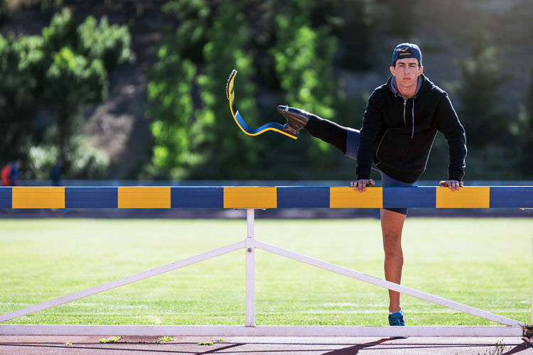 Portrait of young athlete stretching prosthetic leg on railing at running track