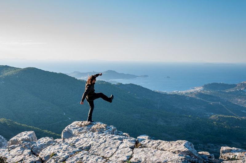Man standing on rock at mountain peak against sky