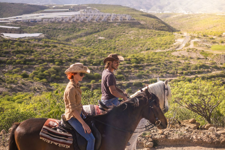 Friends riding horses on mountain