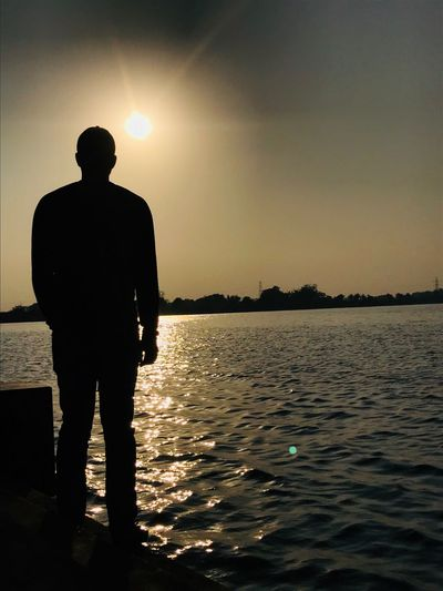 Light and hope. Silhouette Sunset Water Full Length Standing Sun Real People One Person Tranquility Nature Tranquil Scene Rear View Sky Scenics Sunlight Outdoors Sea Men Lifestyles Beauty In Nature
